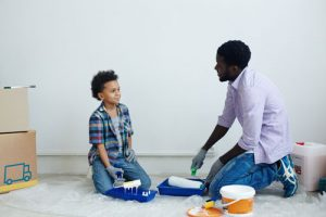 Father and son prepare to paint a wall